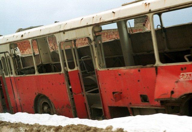 Vrak autobusu na sarajevském sídlišti poničeném dělostřeleckou palbou během bosenské války v roce 1992