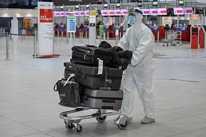 Cestující v ochranném obleku, s rouškou a štítem na snímku pořízeném 21. prosince 2020 v odletové hale Letiště Václava Havla v Praze.