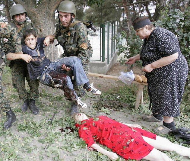 Gruzínští vojáci pomáhají malému chlapci, kterého našli u těla jeho matky.