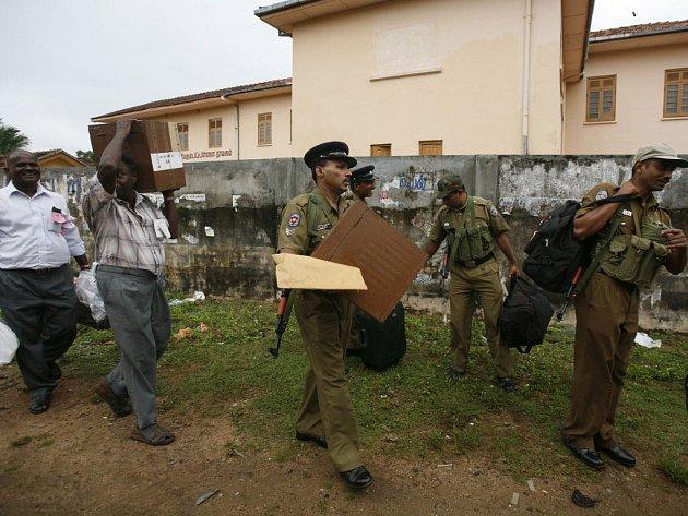 Policisté a volební úředníci odnášejí plné urny do centra v Batticaloa.
