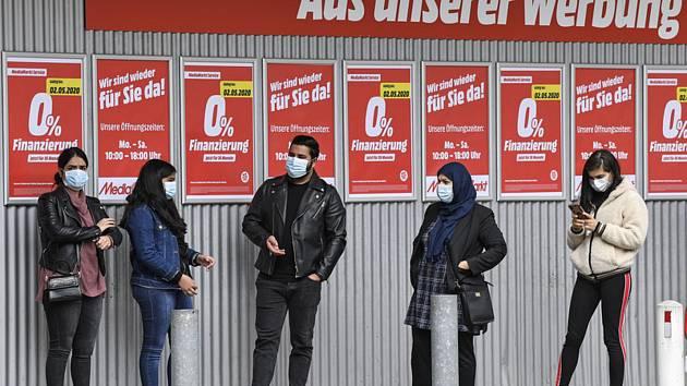 Zákazníci v rouškách čekají ve frontě před obchodem s elektronikou v německém Essenu (na snímku z 29. dubna 2020)