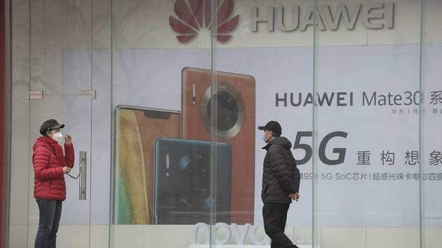 Lidé v rouškách před reklamním billboardem společnosti Huawei v Pekingu