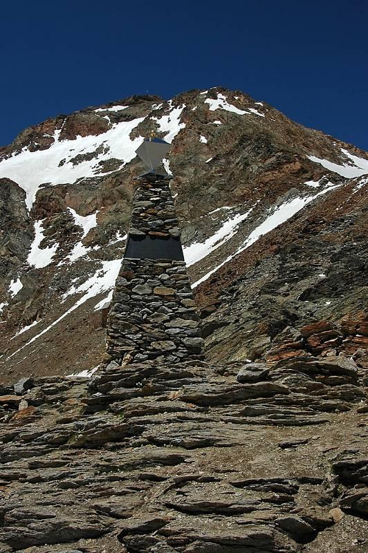 Ötziho památník v Alpách  u Tisenjoch. Ötzi byl nalezen asi 70 m severovýchodně odsud, místo je označeno červenou značkou. Hora v pozadí je Fineilspitze