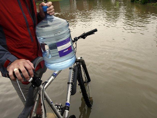 Muž si převáží pitnou vodu do svého zaplaveného obydlí.