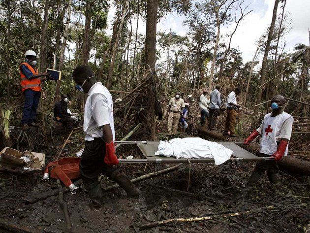 Záchranáří odnášejí lidské ostatky, které vyprostili z trosek letadla.