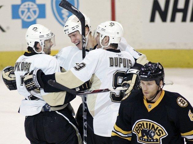 Hokejisté Pittsburghu (zleva Petr Sýkora, Jordan Staal a Pascal Dupuis) se radují ze Sýkorova vítězného gólu v zápase proti Bostonu. V popředí snímku zklamaný Dennis Wideman.