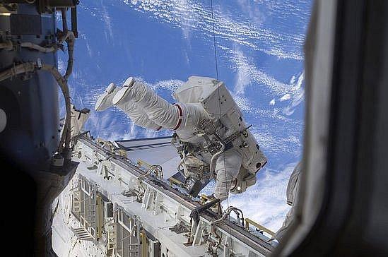 Astronaut Niclole Stott  pracuje ve volném kosmickém prostoru