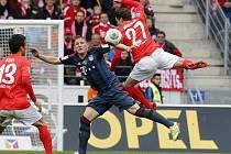 Nicolai Müller z Mohuče (vpravo) se snaží prosadit přes Bastiana Schweinsteigera z Bayernu Mnichov (uprostřed).
