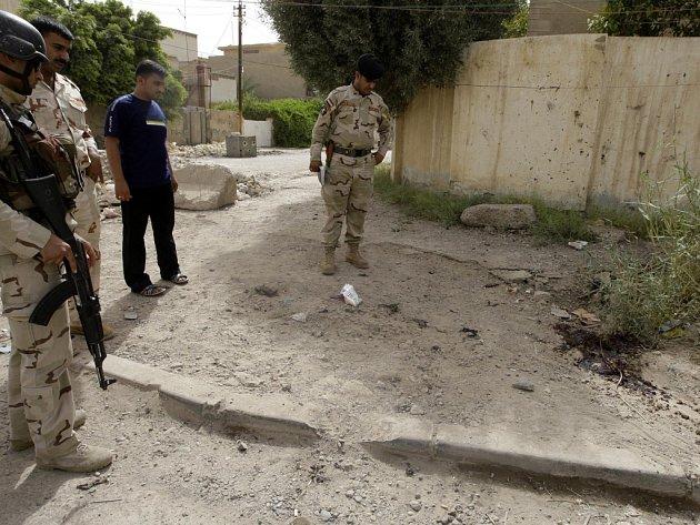 Iráčtí policisté prohlížejí kaluž krve na místě pátečního atentátu v Bagdádu.