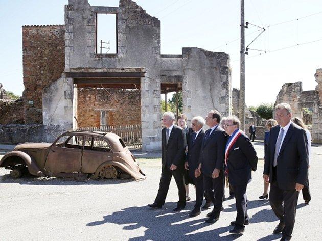 """Německý prezident Joachim Gauck (vlevo) dnes v troskách francouzské vesnice Oradour-sur-Glane, vyhlazené v roce 1944 nacisty, poděkoval přítomným přeživším a pozůstalým za """"vůli k usmíření""""."""