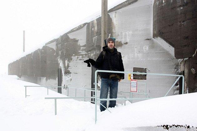 Poutník v záplavě sněhu a betonu. Za ním se tyčí zapadaná pevnost Dobrošov.
