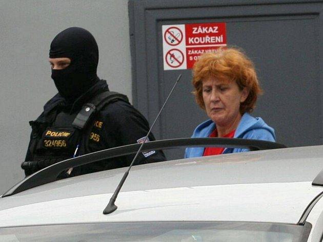 Policie vede ženu obviněnou z vraždy od soudu.