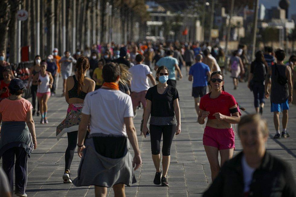Lidé se procházejí 2. května 2020 na přímořské promenádě v Barceloně