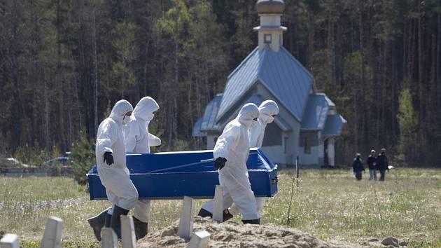 Pohřební zřízenci nesou na hřbitově ve městě Kolpino rakev s obětí koronaviru.