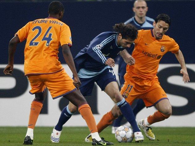 Halil Altintop ze Schalke (vmodrém) vobležení barcelonských hráčů Tourého a Zambrotty.