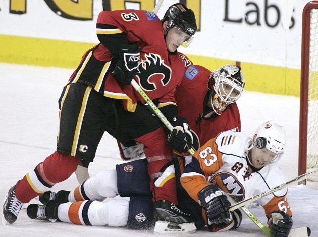 Český hokejista Josef Vašíček bojuje o puk s Dionem Phaneufem z Calgary. New York Islanders se nakonec radovali z vítězství nad Flames 4:3 až po samostatných nájezdech.