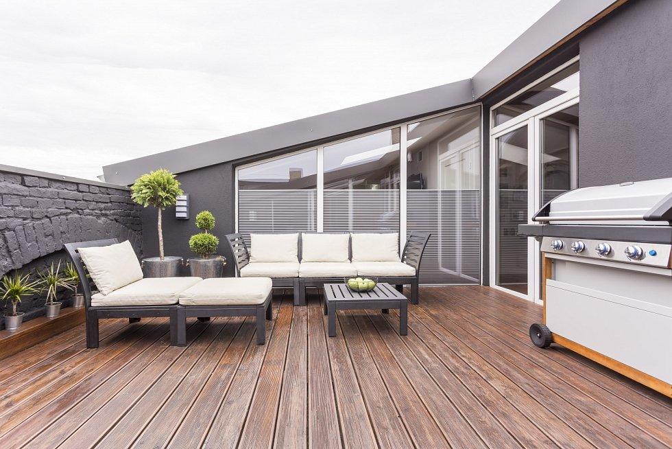 Světlý zahradní nábytek, gril a rostliny na útulné terase s dřevěnou podlahou a cihlovou zdí