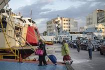 Lidé v rouškách nastupují na palubu trajektu v řeckém přístavu Pireus