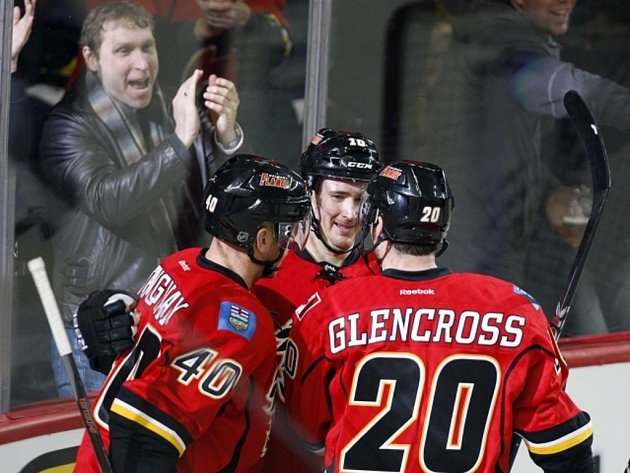 Hokejisté Calgary (zleva) Alex Tanguay, Roman Červenka a Curtis Glencross se radují z gólu.