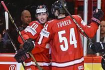 Hokejisté Švýcarska Denis Hollenstein (vlevo) a Philippe Furrer se radují z gólu proti Kanadě.