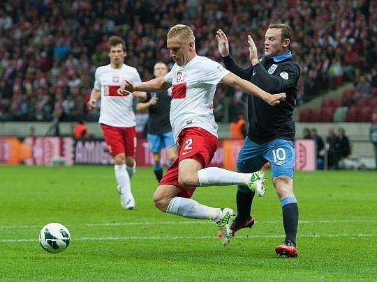 Polák Glik odehrává míč před uzdraveným útočníkem Anglie Waynem Rooneym.