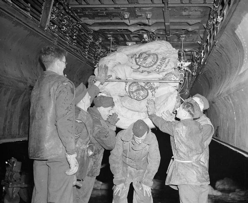 Vojáci nakládají zásoby jídla do bombardovacího letadla Lancaster britské RAF