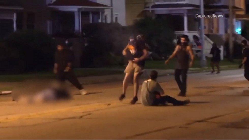 Po střelbě se Kyle Rittenhouse začal zvedat, muž vpravo zvedl paže na znamení, že nemá zbraň