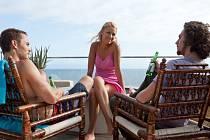 TROJKA NA HRANĚ. Hrdinové bestselleru Divoši a stejnojmenného Stoneova filmu zatím ještě prožívají idylku v kalifornském apartmá nad oceánem.