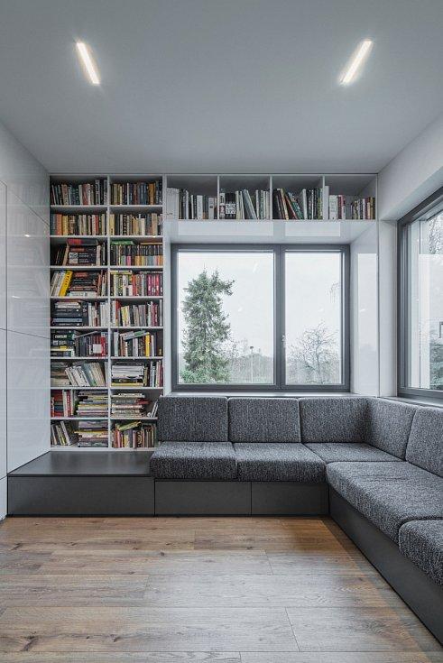V obývacím pokoji zaujme velká rohová vestavěná sedačka u oken.