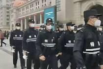 Policisté s maskami před nádražím ve městě Wu-chan