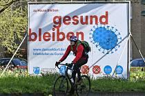 """Cyklista projíždí 23. března 2020 kolem billboardu v německém Düsseldorfu, kde je napsáno """"zůstaň doma, zůstaň zdravý""""."""