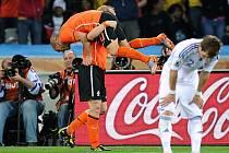 Nizozemci Wesley Sneijder (nahoře) a Dirk Kuyt slaví gól proti Slovensku. Vlevo smutný obránce Peter Pekarík.
