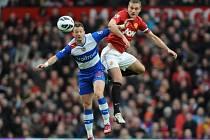 Nemanja Vidic z Manchesteru United v hlavičkovém souboji s Noelem Huntem z Readingu.