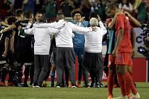 Fotbalisté Mexika se radují z výhry, vpravo zklamaní hráči USA.