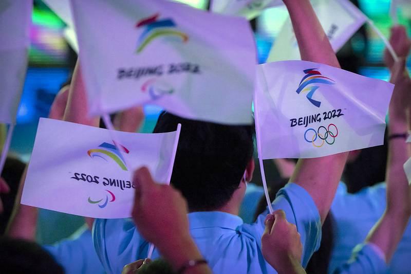 Účastníci mávají s vlaječkami s logy zimních olympijských her a paralympiády v Pekingu 2022.