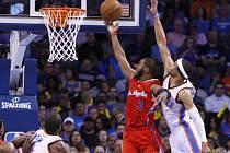 Chris Paul z LA Clippers (v červeném) se prosazuje přes bránícího Russella Westbrooka z Oklahomy.