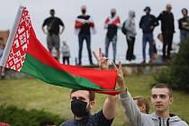 Lidé s běloruskou vlajkou protestují 12. srpna 2020 v ulicích Minsku.