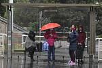 Lidé se kryjí na zastávce před deštěm