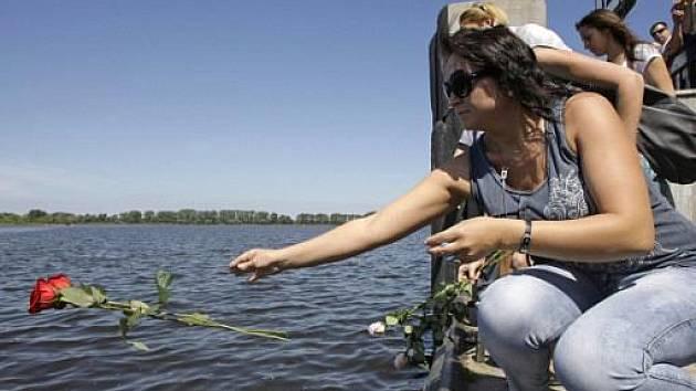Lidé házejí květiny do řeky Volhy.