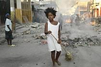 Žena uklízí trosky na jedné z ulic haitského hlavního města Port-au-Prince.