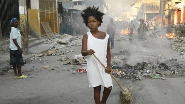 acc5f00ef Žena uklízí trosky na jedné z ulic haitského hlavního města Port-au-Prince.  ...
