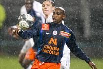Počasí v Lyonu fotbalu příliš nepřálo. Na snímku bojují o míč domácí Kim Källström a útočník Montpellier Souleymane Camara (vpředu).