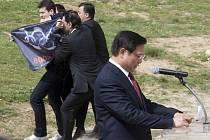 Protibetský demonstrant je odváděn policisty během projevu prezidenta organizačního výboru her v Pekingu Liou Čchi.