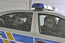 Okresní soud v Ostravě rozhoduje o vazbě pro sedm obviněných v kauze šéfky kabinetu premiéra Jany Nagyové. Na snímku z 15. června přivážejí policisté jednoho z obviněmých, zřejmě šéfa Vojenského zpravodajství Milana Kovandu (vlevo).