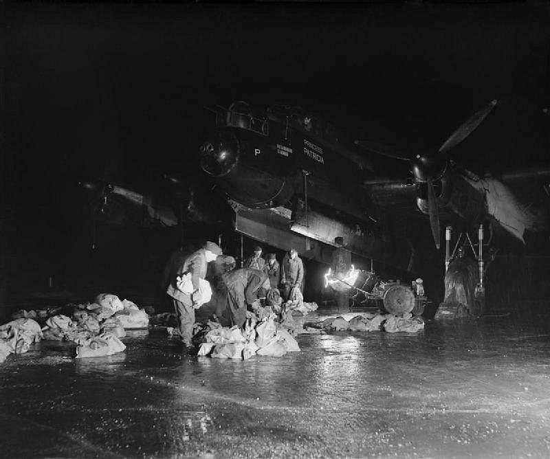 Vojáci nakládají zásoby na palubu bombardéru RAF Lancaster