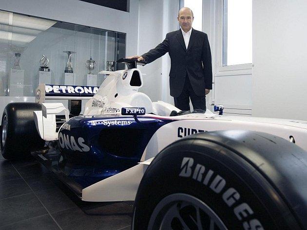 Švýcar Peter Sauber pózuje u staršího modelu vozu formule 1 během tiskové konference.