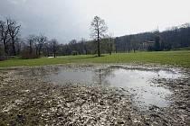 Obrovská louže a rozbahněná půda na místě po propadu zeminy v pražském parku Stromovka