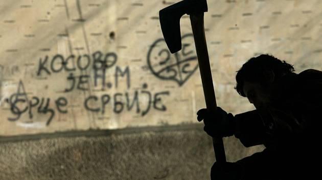 Muž štípe dříví před nápisem: Kosovo je srdcem Srbska