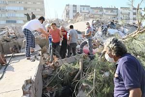 Lidé v tureckém městě Izmir prohrabávají sutiny po zemětřesení.