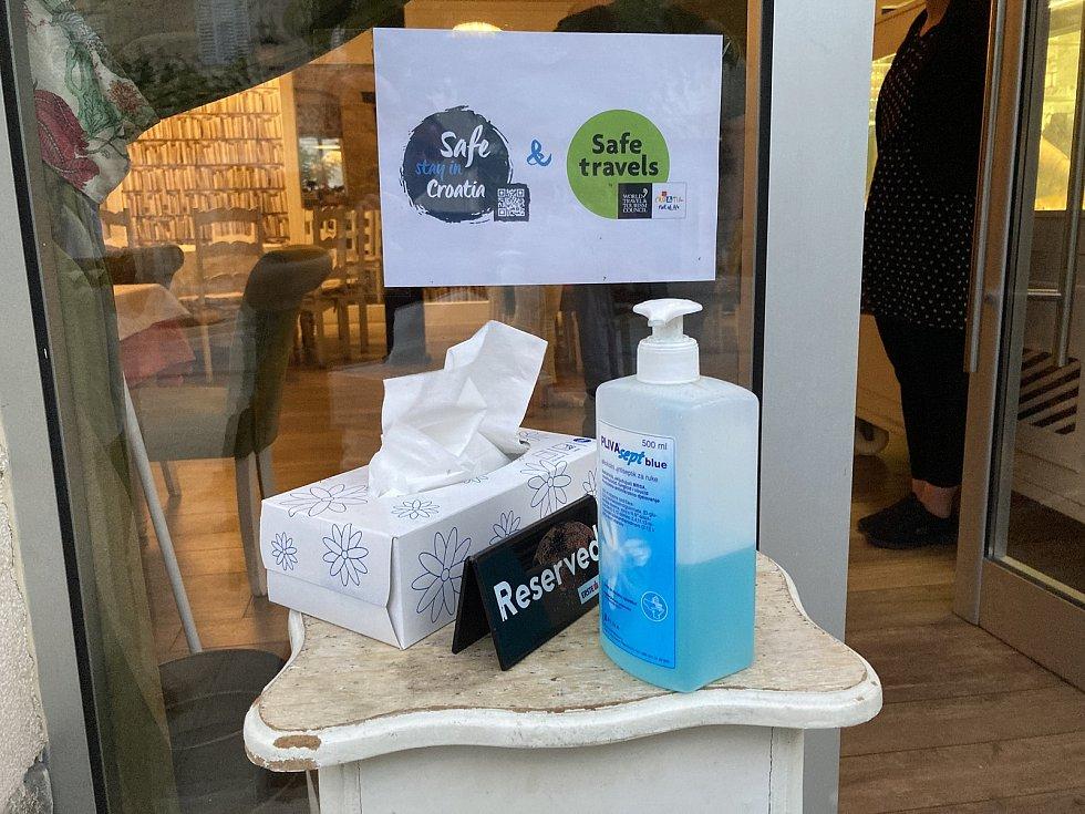 Pečlivě připravené hygienické prostředky. To je obvyklý obrázek před restaurací ve Splitu. Hostinští věří, že jim letošní sezonu již koronavirus nepřekazí.